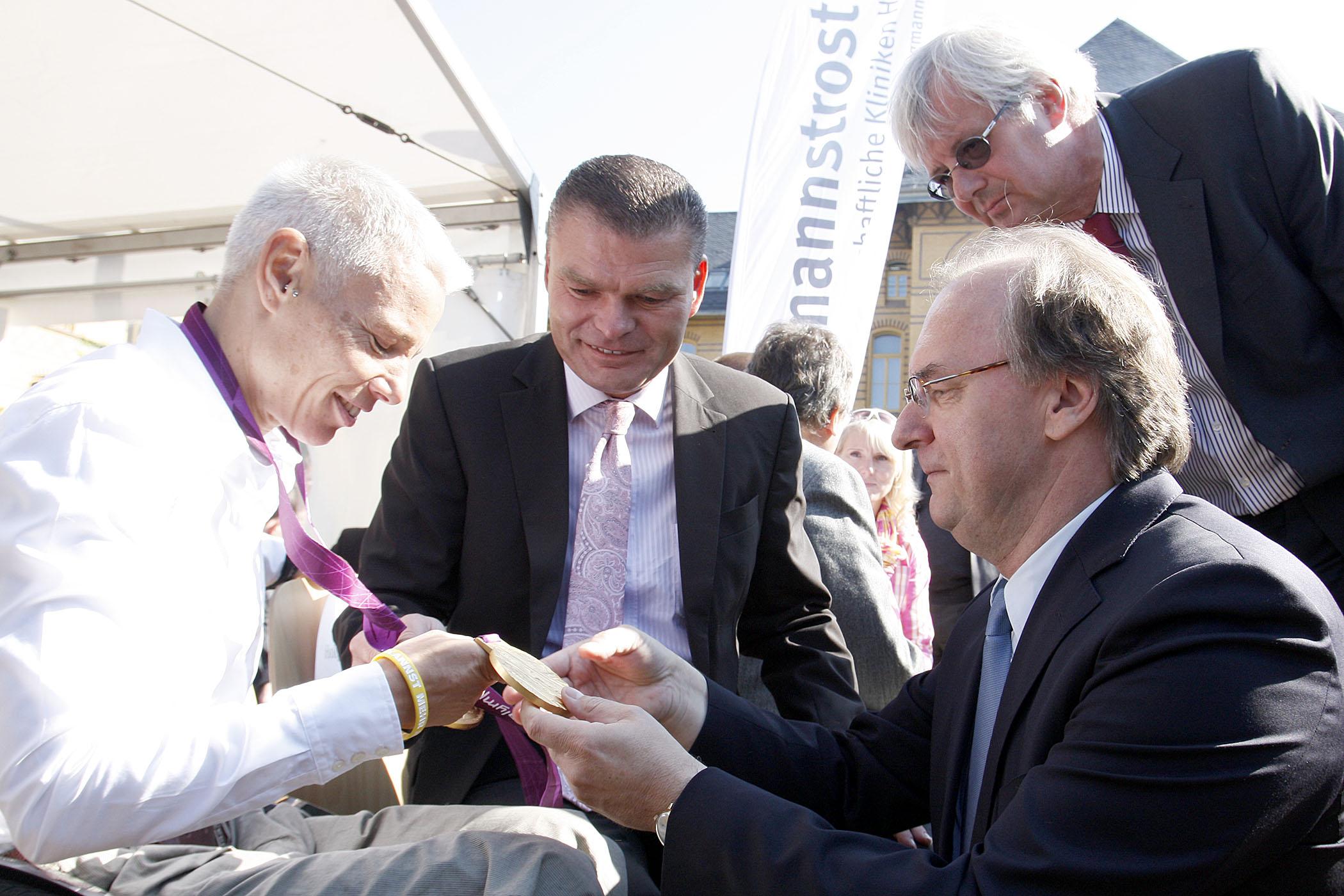 Andrea Eskau zeigt ihre beiden paralympischen Goldmedaillen Innenminister Holger Stahlknecht und Ministerpräsident Rainer Haselhoff